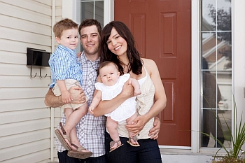 Young family in front of their new home rental in Orange County